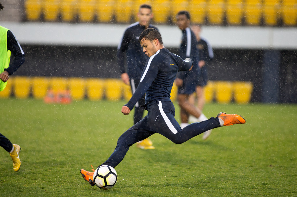Photo of a student kicking a soccer ball.