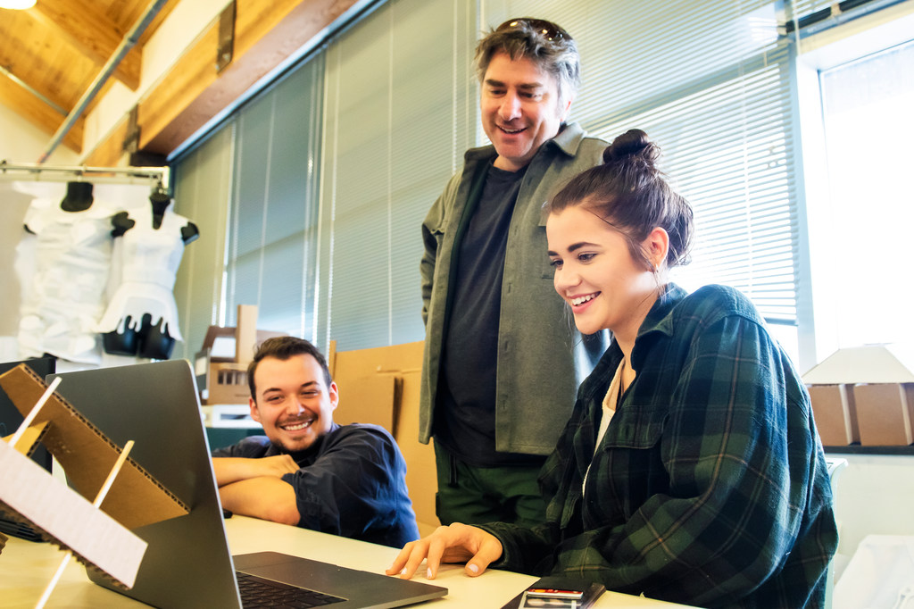 Three people in front of a laptop