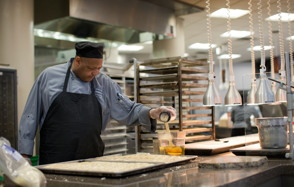 Man pours powder to make a sauce while working in the dining hall kitchen.