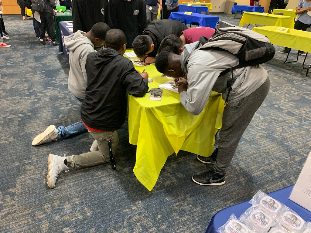 High school students kneeling around a table filling out info cards for the U.S. Army at the Middle College Career Expo.