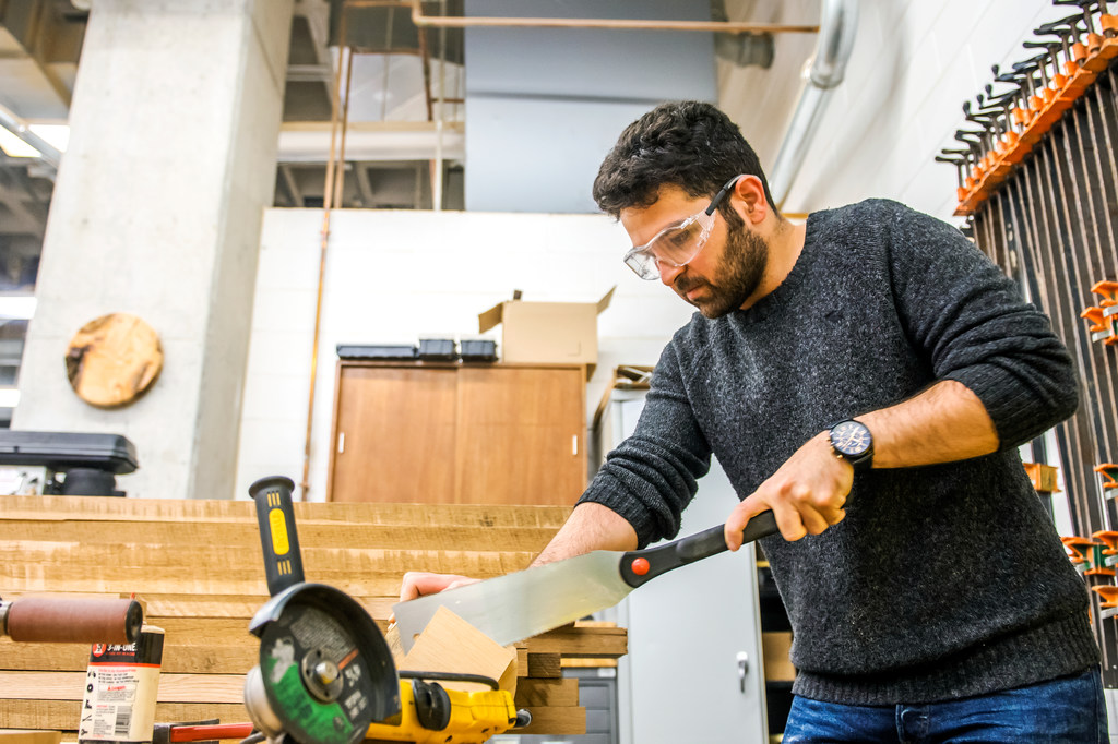 Student cutting wood with what looks like a giant knife in Gatewood Arts Studio Building wood shop. He's wearing protective goggles.