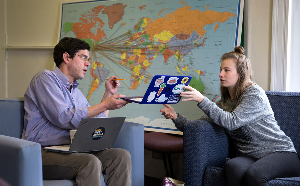 Two people sitting in front of a world map