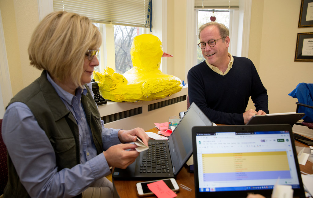 Two people at a desk. A large paper mache duck sits in the window.
