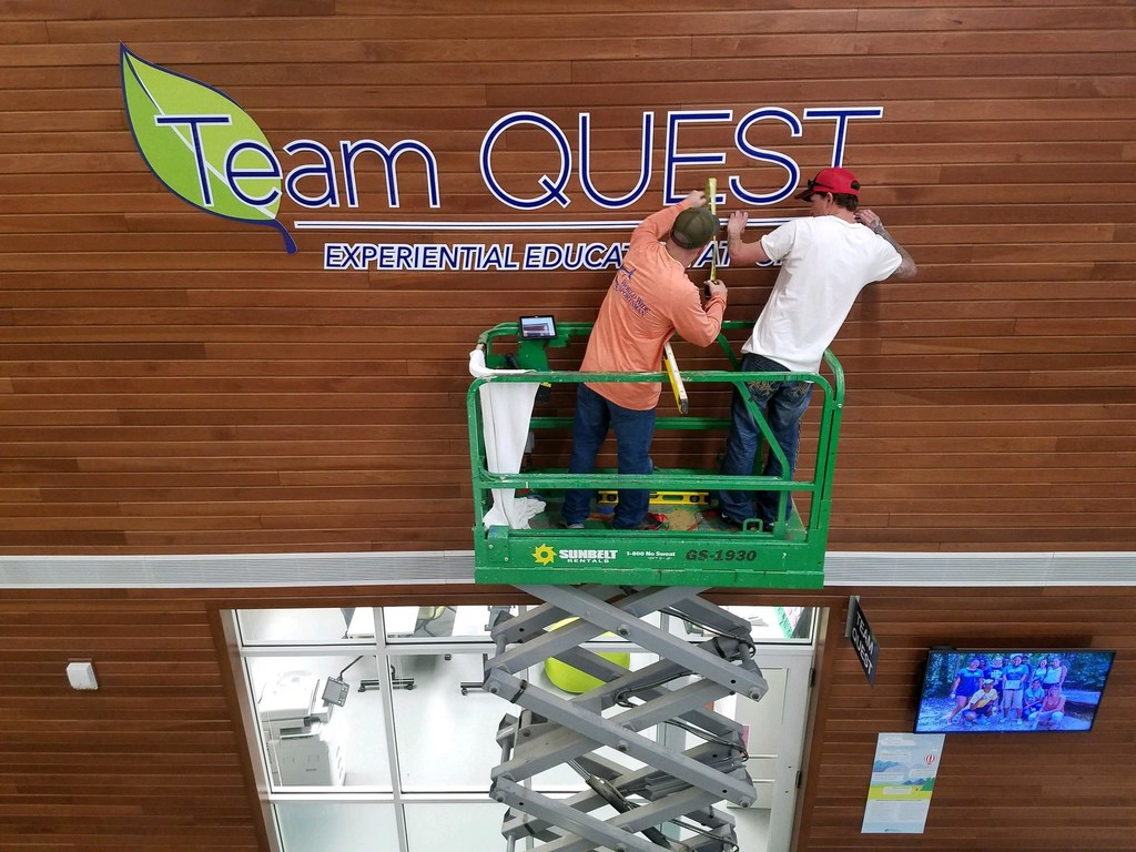 "Two male workers on a green lift install a blue and green sign on a wooden panel wall that reads ""Team QUEST"" inside the Kaplan Center."