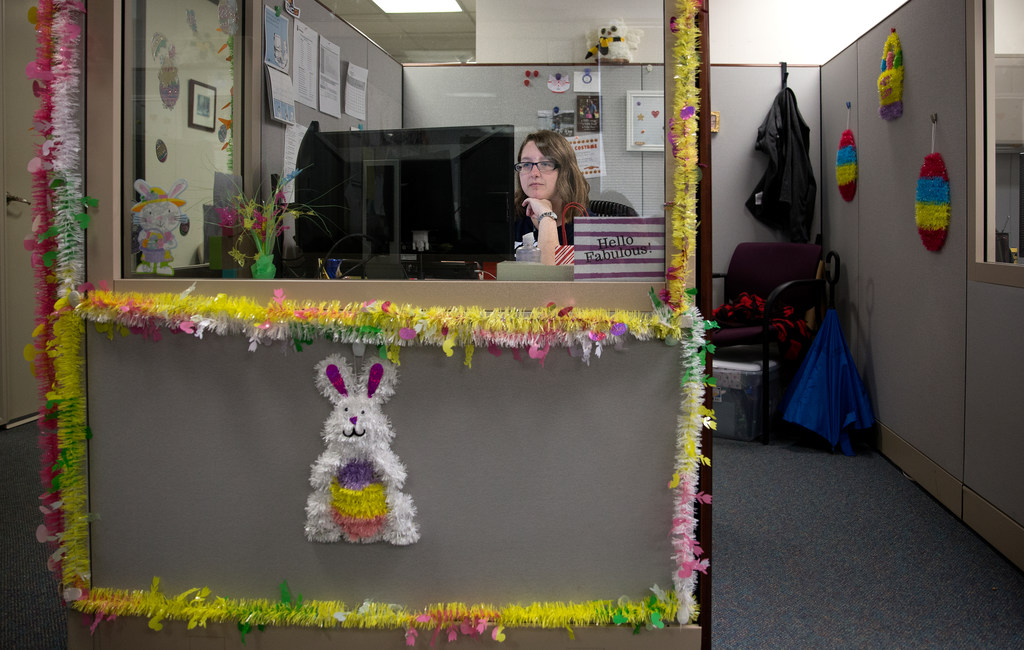 Jillian Lincourt sits behind her desk in the Registrar's Office. The desk is decorated with brightly colored fringe and has an Easter bunny on the front,