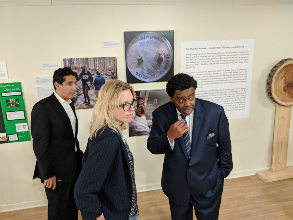 Dr. Omar Ali, Dr. Nadja Cech, and Chancellor Gilliam stand in front of a wall displaying scientific images.