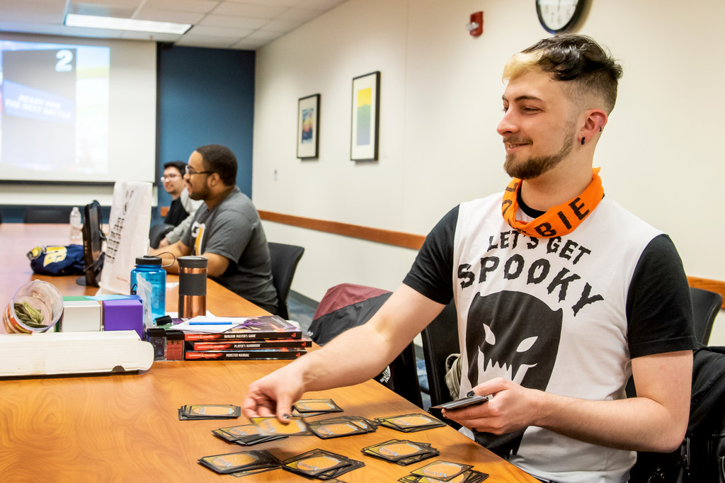 Phillip Jones, a computer science major and club president, distributes cards to play a 'Magic The Gathering' card game.