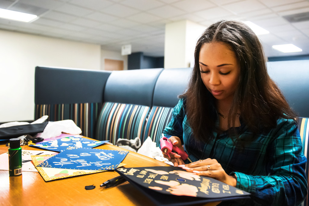Siara Burwell decorates graduation caps for graduating UNCG students.