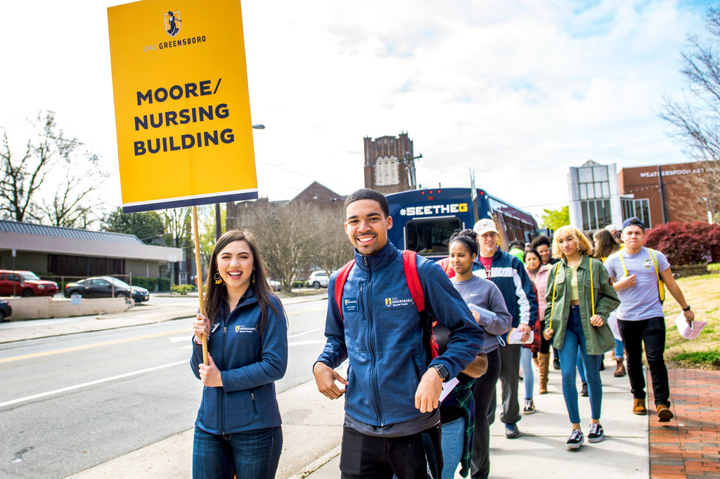 Diana Huynh, a junior nursing major and Spartan Guide, and Dylan Dodson, a sophomore geography student and Spartan Guide, lead the way to Moore Nursing Building from UNCG Auditorium.
