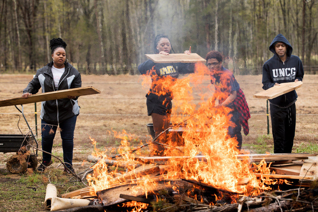 Deanna Spann, Anabelle Charles, Kalonji Jegede-Roberts and Josh Kebreau (l-r), discard old scrap wood. These UNCG students are taking part in a monthly service day event in the Catalyst program.