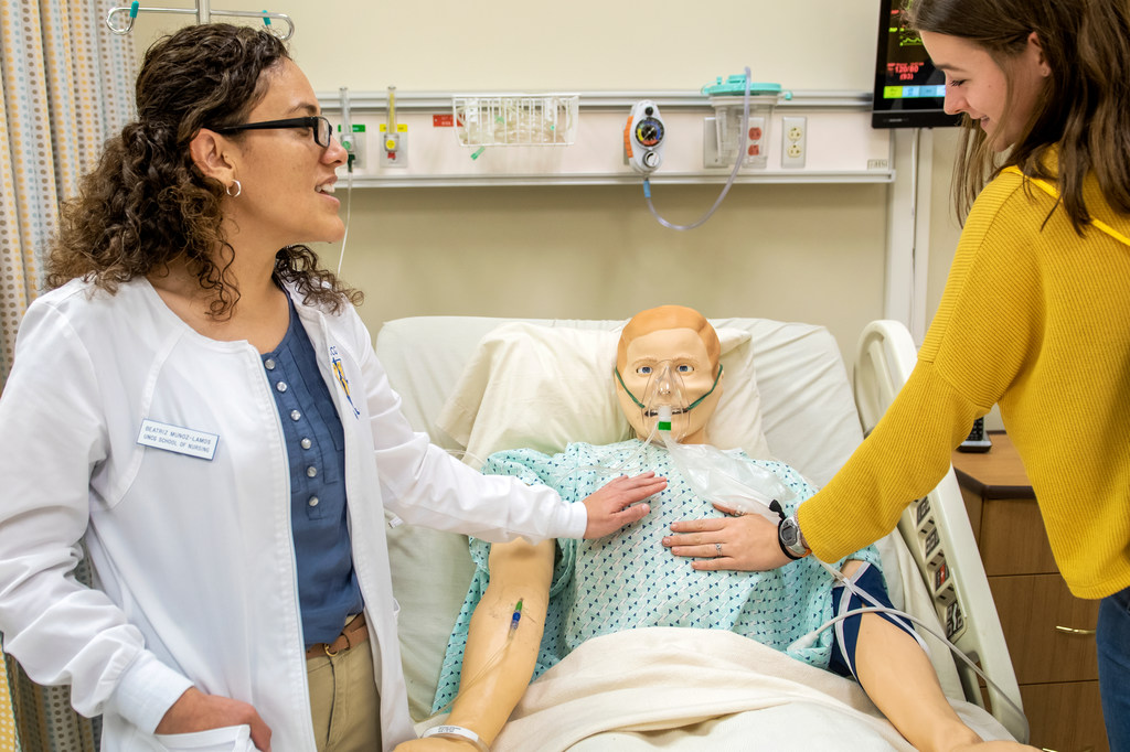 Two women place their hands on a mannequin in a nursing simulation lab at UNCG.
