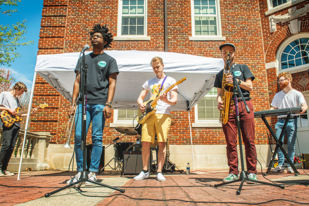 Shown are five members of a band performing on the patio of Mary Foust Residence Hall.