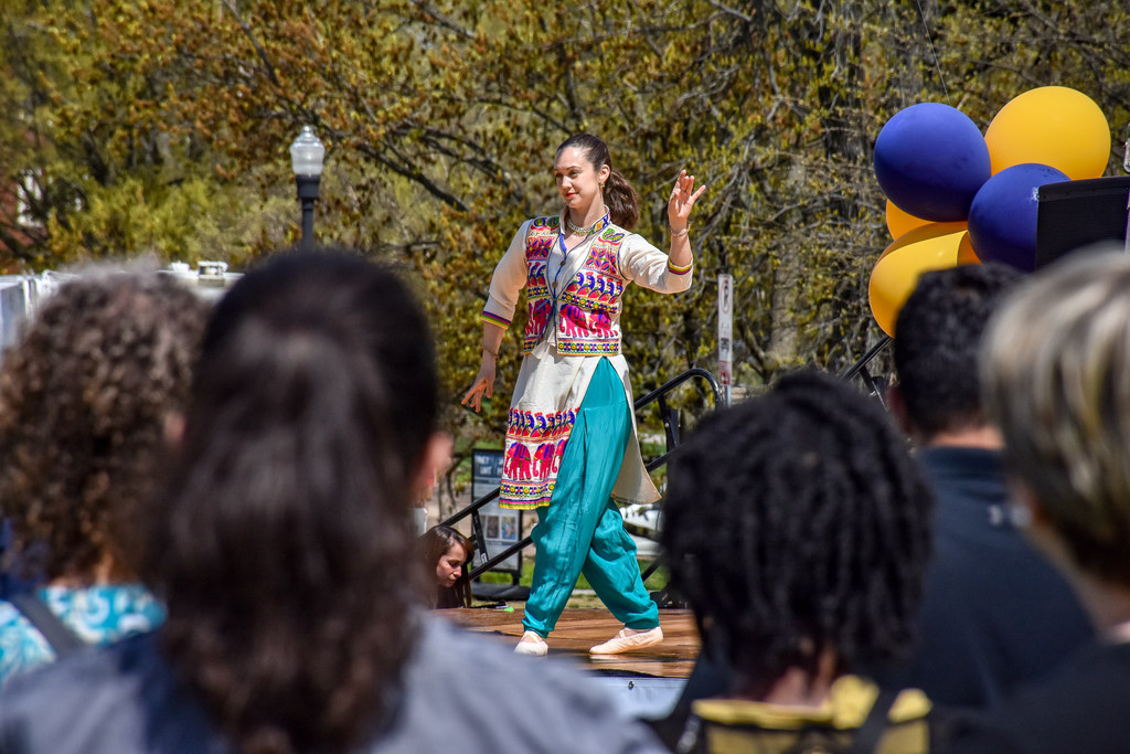 People in the foreground watch a woman perform a classical Indian dance on stage.