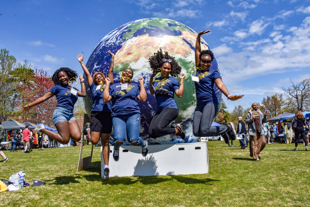 Five women wearing blue shirts and name tags jump in unison on the lawn in front of the Elliott University Center, during the International Festival.