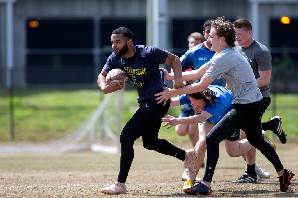 A man with a ball in his hand (facing left) runs while other rugby players try to tackle him on the recreation field at UNCG.