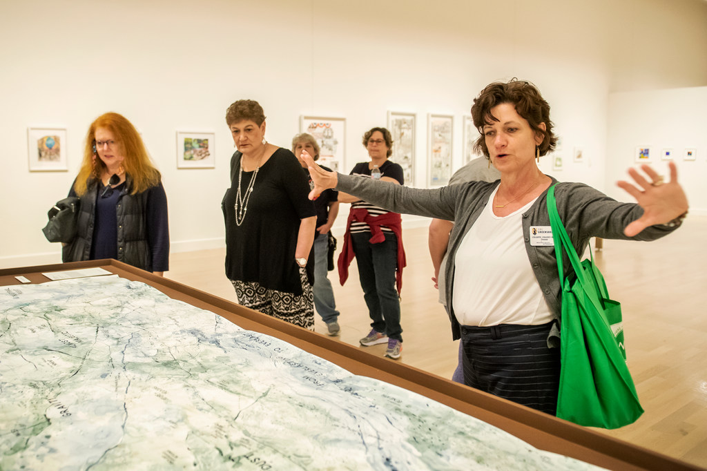 A woman (right) extends her arms to show an art piece at Weatherspoon Art Museum at UNCG. Four women look on behind her.