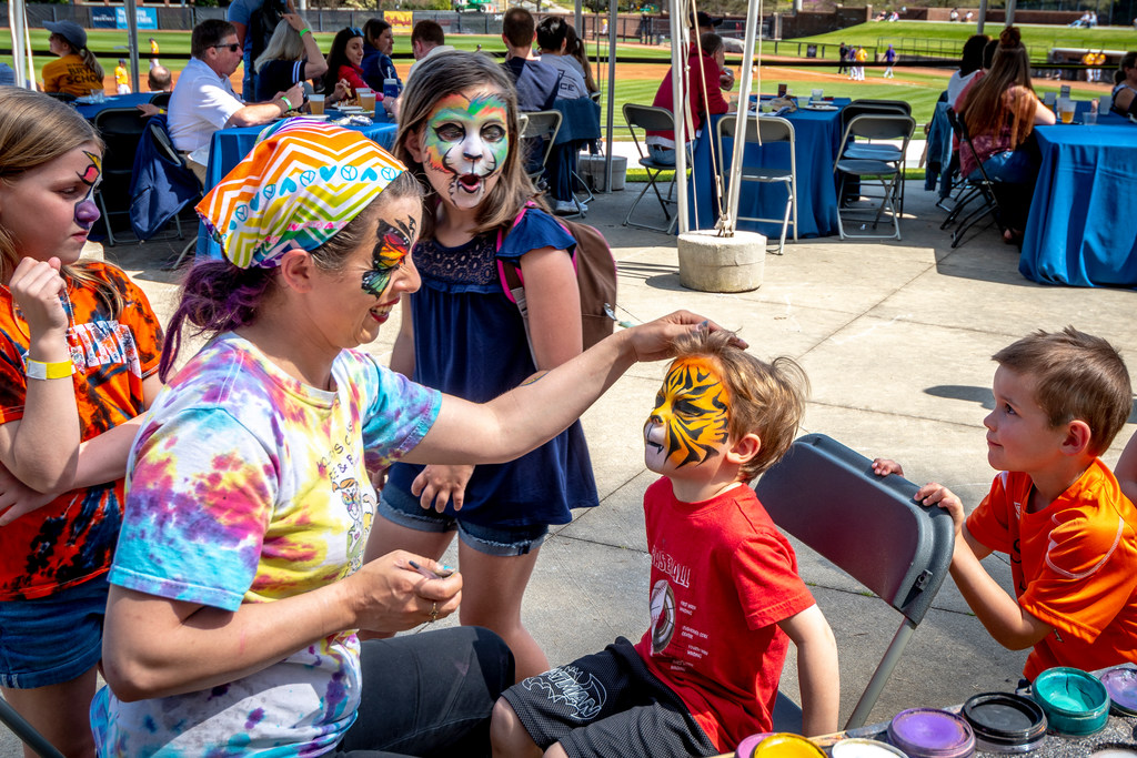 A woman paints a tiger design on the face of a child attending a baseball game at UNCG. Three other children look on.