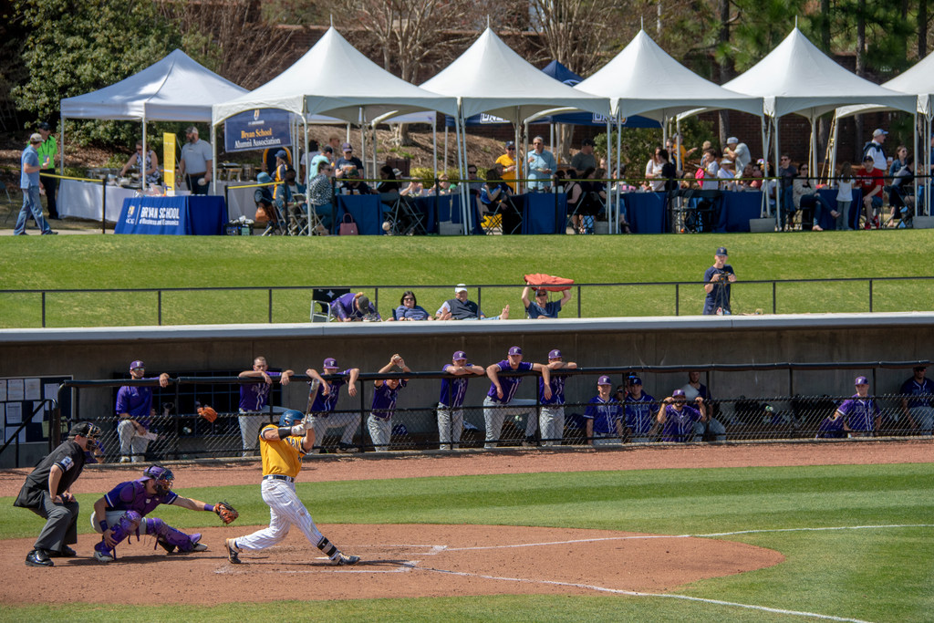 A UNCG baseball player swings his bat as people under large tents watch from behind.