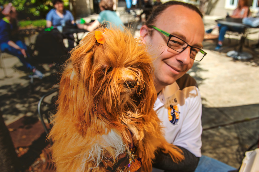 A man holding a red, long-haired dog, poses in front of the camera.