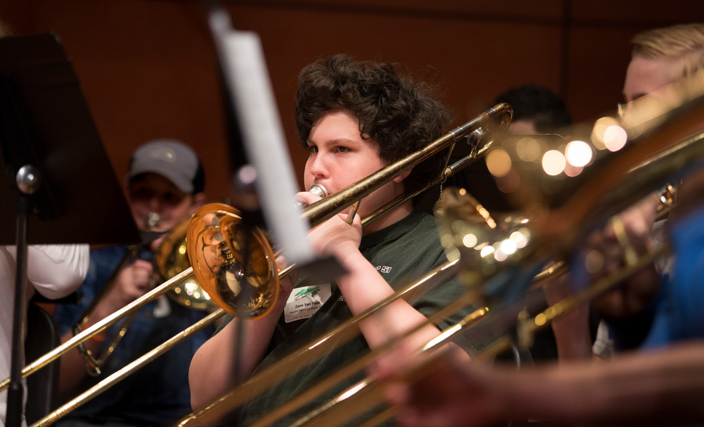 A closeup shot of a middle school student playing a trombone during practice at a Trombone Festival held in UNCG's Music Building.