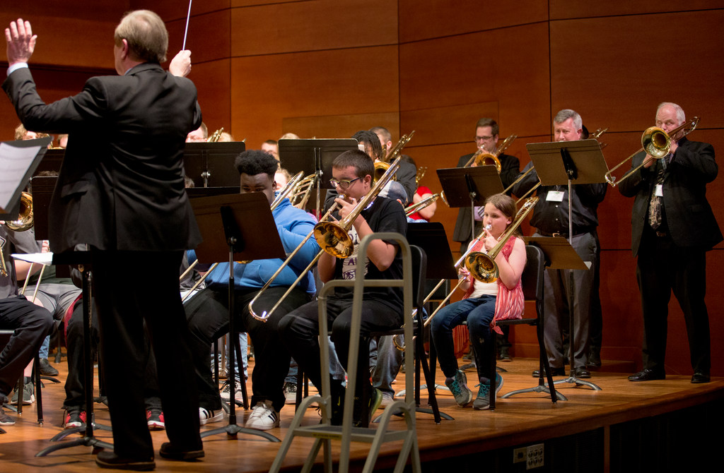 A man waves his arms as he conducts a trombone choir on stage in the UNCG Music Building.